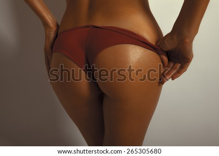 Sexy woman buttock on white background. Tanned skin. Horizontal shot, soft colors - stock photo