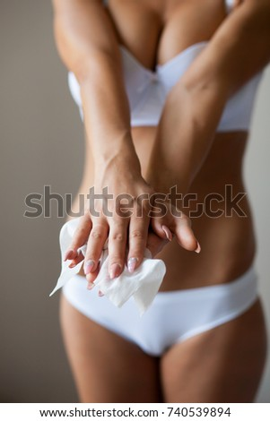 Sexy woman clean hands with wet wipes, body breast lingerie panties in blurred background