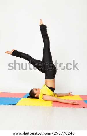 Sexy woman doing yoga exercises on a mat color.