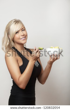sexy woman eating from a bowl of fresh fruit - stock photo