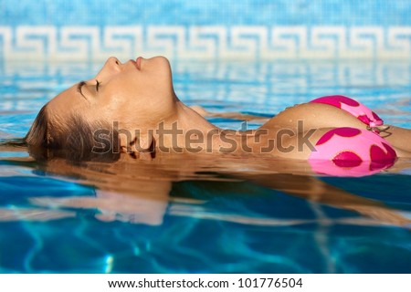 Sexy woman enjoying summer sun in outdoor swimming pool. - stock photo
