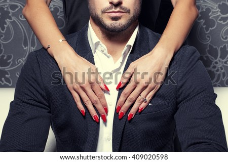 Sexy woman hands with red nails embrace rich man - stock photo