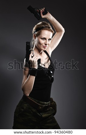 Sexy woman holding gun on gray - stock photo