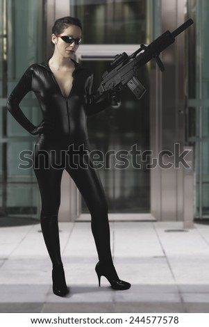 Sexy woman holding gun wearing a black leather dress - stock photo