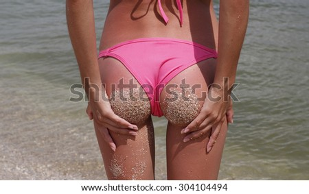 Sexy woman holding her ass in swimwear at seaside  - stock photo