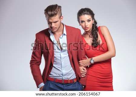 sexy woman holding her man by arm, on gray studio background