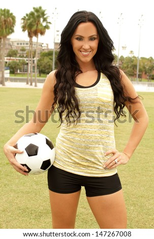 Sexy woman holding soccer ball in her hand in playing field - stock photo