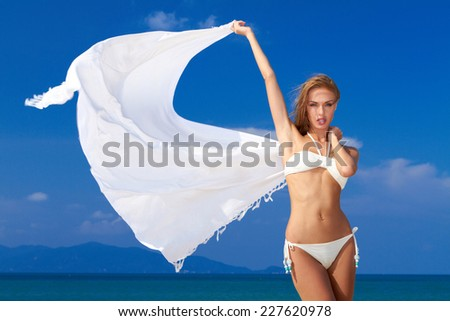 Sexy woman in a bikini with a white scarf held high in her hands blowing in the wind against a sunny blue tropical sky and ocean - stock photo