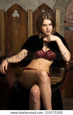 Sexy woman in a medieval castle interior - stock photo