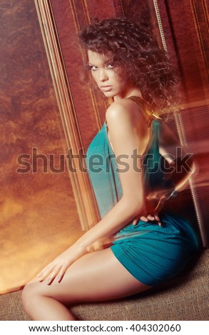Sexy woman in azure dress posing on camera. - stock photo