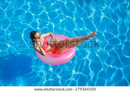 Sexy woman in bikini enjoying summer sun and tanning during holidays in pool with cocktail. Top view. Woman in swimming pool. Sexy woman in bikini. - stock photo