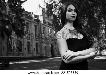 sexy woman in black dress and necklace near old building  black and white photo