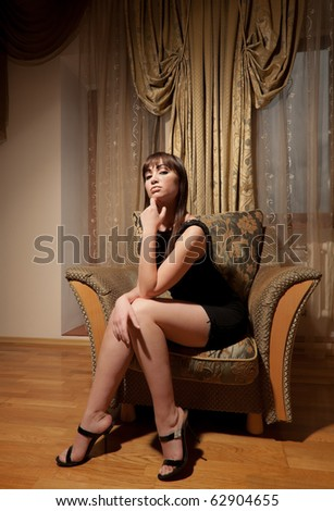 Sexy woman in black dress sitting on the armchair - stock photo