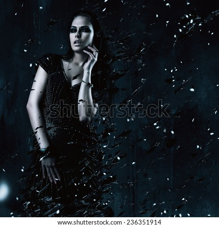 sexy woman in black dress with broken glass around in dark room - stock photo