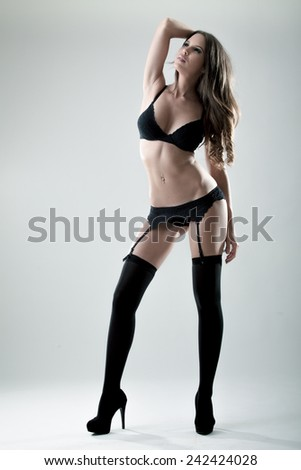Sexy woman in black lingerie and black stockings in studio - stock photo