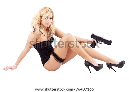 Sexy woman in black lingerie holding pistol, sitting position - stock photo