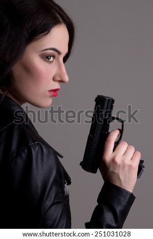 sexy woman in black with gun over grey background - stock photo