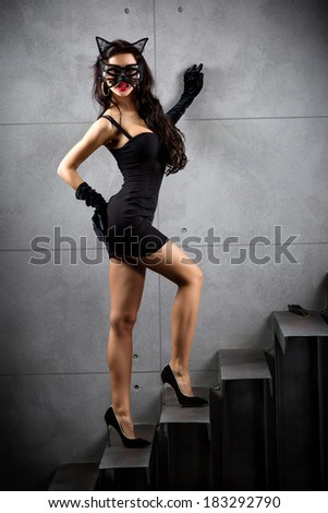 sexy woman in catwoman suit staying on stairs at backyard of building - stock photo