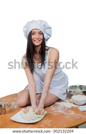 sexy woman in chef uniform knead the dough - stock photo