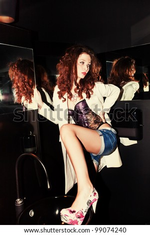 sexy woman in corset, shorts and high heel shoes in toilet - stock photo
