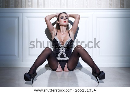 Sexy woman in corset sitting on floor at vintage wall - stock photo
