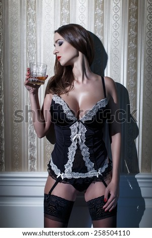 Sexy woman in corset with whiskey at vintage wall - stock photo