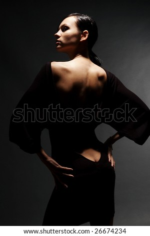 sexy woman in dress with naked back against dark background - stock photo