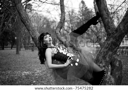 Sexy woman in fashionable clothing lying on a tree branch, black and white - stock photo