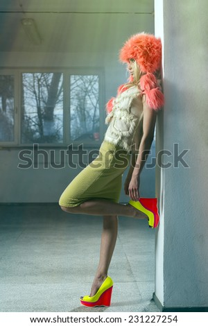 Sexy woman in fluorescent clothes posing in empty hall - stock photo