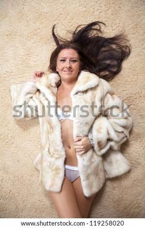 Sexy woman in fur coat laying over  rug - stock photo