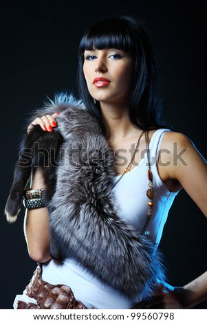 Sexy woman in fur dress against dark background - stock photo