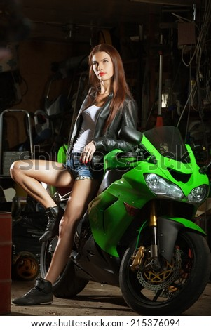 Sexy woman in garage with her sport bike - stock photo