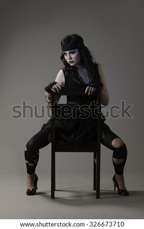 Sexy woman in grungy, rocker girl outfit with headband and torn leggings, sitting on a chair in a provocative manner.