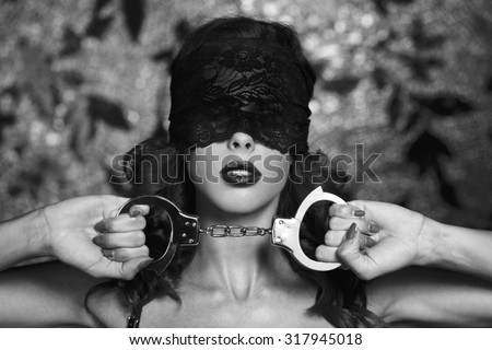 Sexy woman in lace eye cover holding handcuffs, bdsm, black and white - stock photo