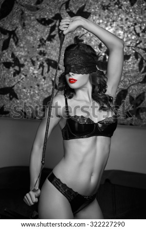 Sexy woman in lace eye cover holding whip, bdsm, black and white, selective coloring - stock photo