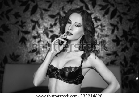Sexy woman in latex bra in bedroom at night, black and white - stock photo