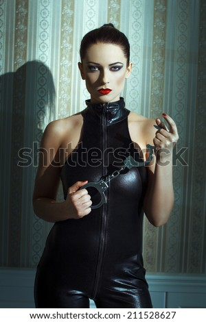 Sexy woman in latex catsuit and handcuffs posing at vintage wall