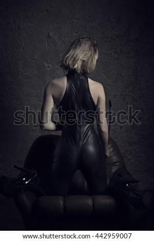 Sexy woman in latex catsuit kneeling on sofa, bdsm