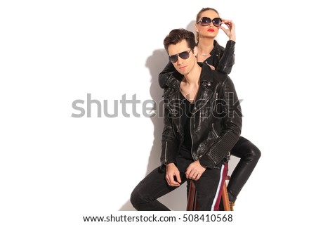 sexy woman in leather jacket leaning her elbow on her boyfriend's back