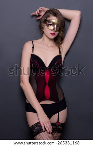 sexy woman in lingerie and mask posing over grey background - stock photo