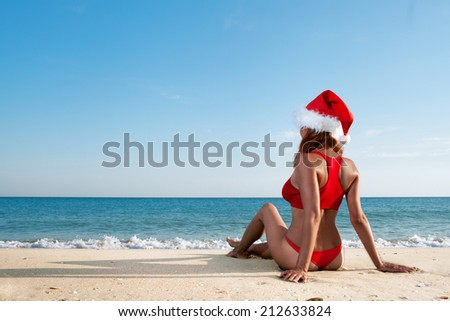 sexy woman in santa hat on sea beach - stock photo