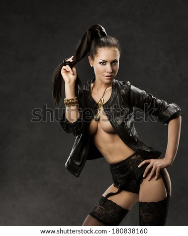 sexy woman in sensual stockings, erotic black leather jacket, over dark background  - stock photo