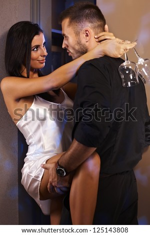 Sexy woman in silk nighty holding champagne flute, embracing with man in black. - stock photo