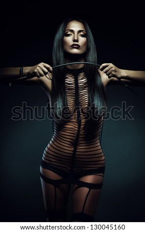 sexy woman in striped costume with whip