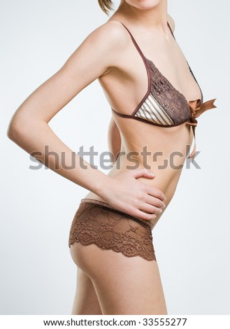 Sexy woman in stylish brown stripped lingerie, studio shot - stock photo