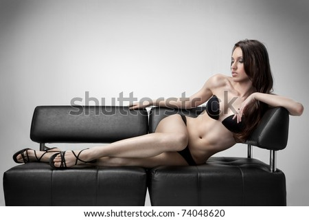sexy woman in swimsuit lies on the sofa