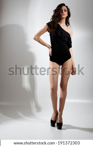 sexy woman in swimsuit posing glamorous in the studio
