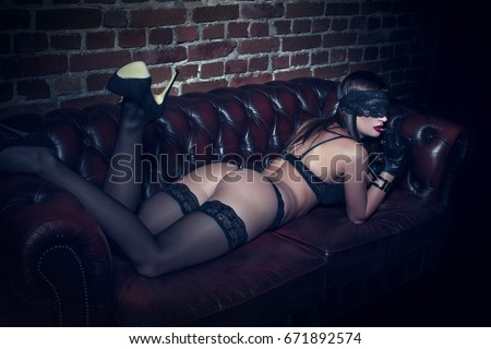 Sexy woman in underwear and blindfold lying on sofa with handcuffs, bdsm