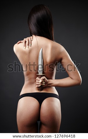 Sexy woman in underwear with her back to camera, hands up, in one hand holding a large knife behind her back. - stock photo