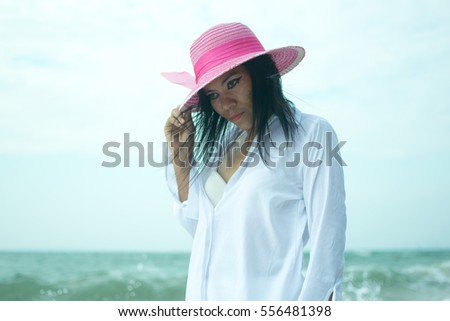 Sexy woman in white shirt posing on the beach